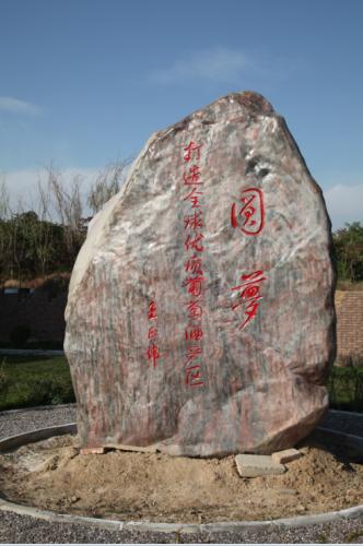 หลักหินที่วางตั้งอยู่หน้าสวนองุ่น มีคำขวัญเขียนไว้ว่า  สวนแห่งความฝัน (园梦) สรรค์สร้างพื้นที่ปลูกองุ่นเพื่อผลิตไวน์ที่ดีที่สุดในโลก